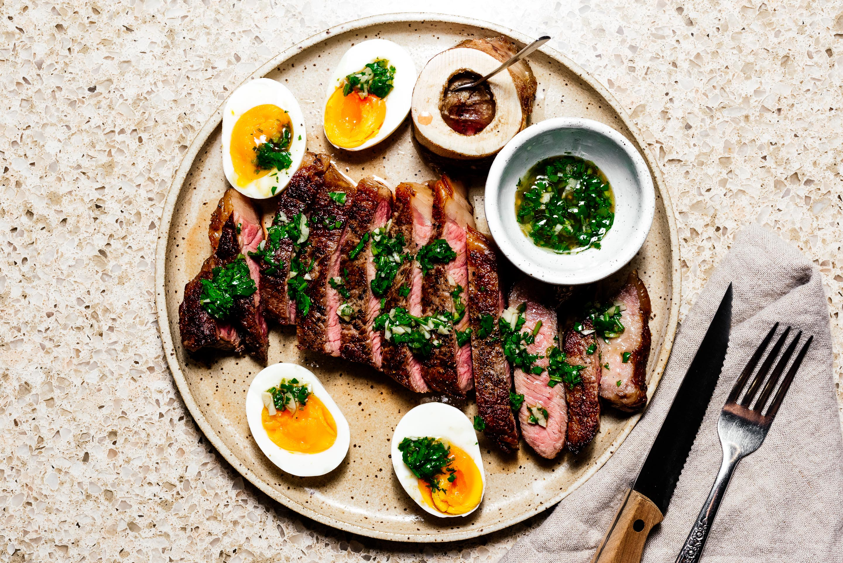 Oven roasted steak with Japanese chimichurri, roasted bone marrow, and jammy eggs