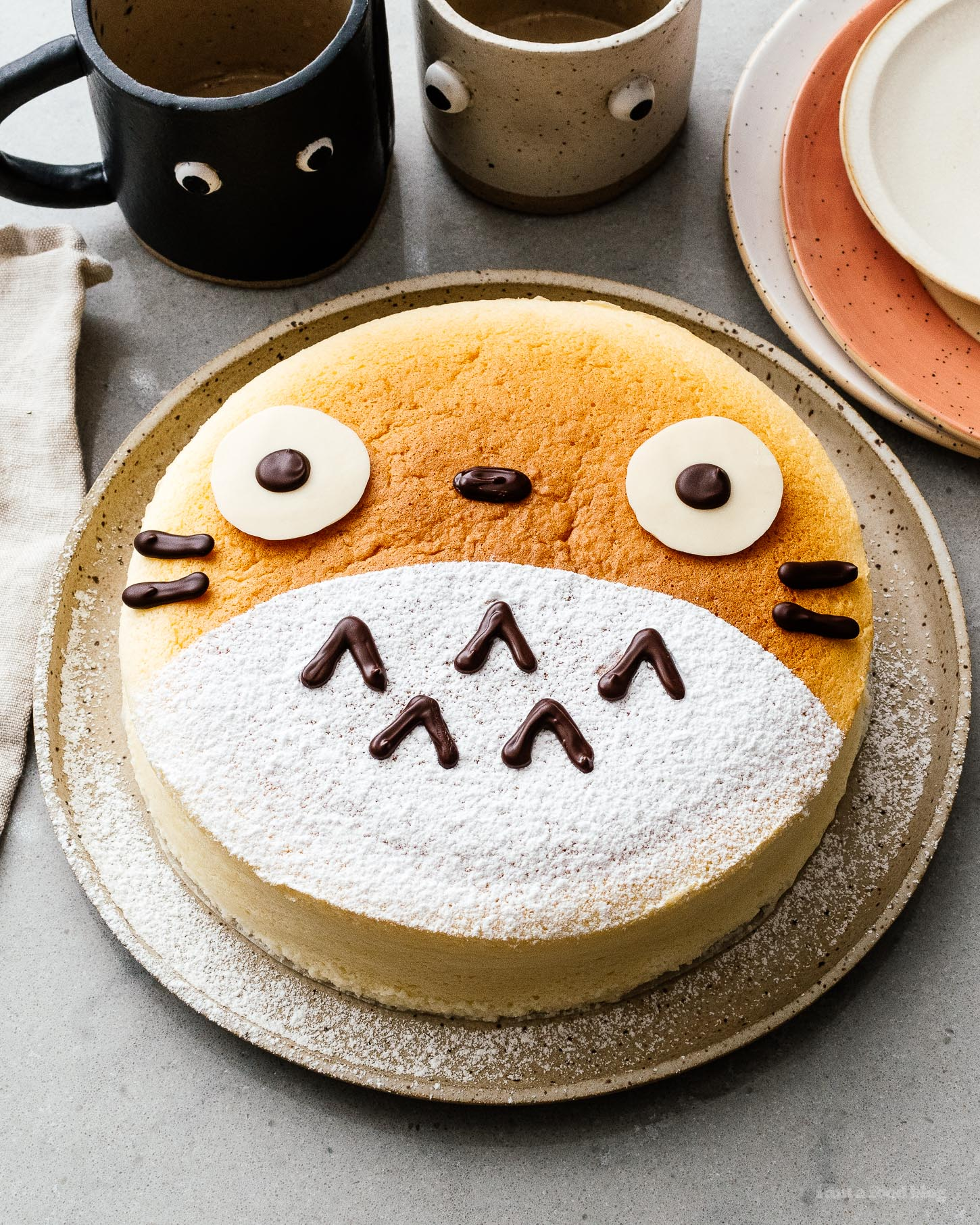A super cute fluffy, jiggly Totoro cheesecake: pillowy soft, cotton-y, light-as-air cheesecake with just a hint of sweetness. #cheesecake #japanesecheesecake #fluffycheesecake #totorocake #totorocheesecake #totorofood #kawaiifood