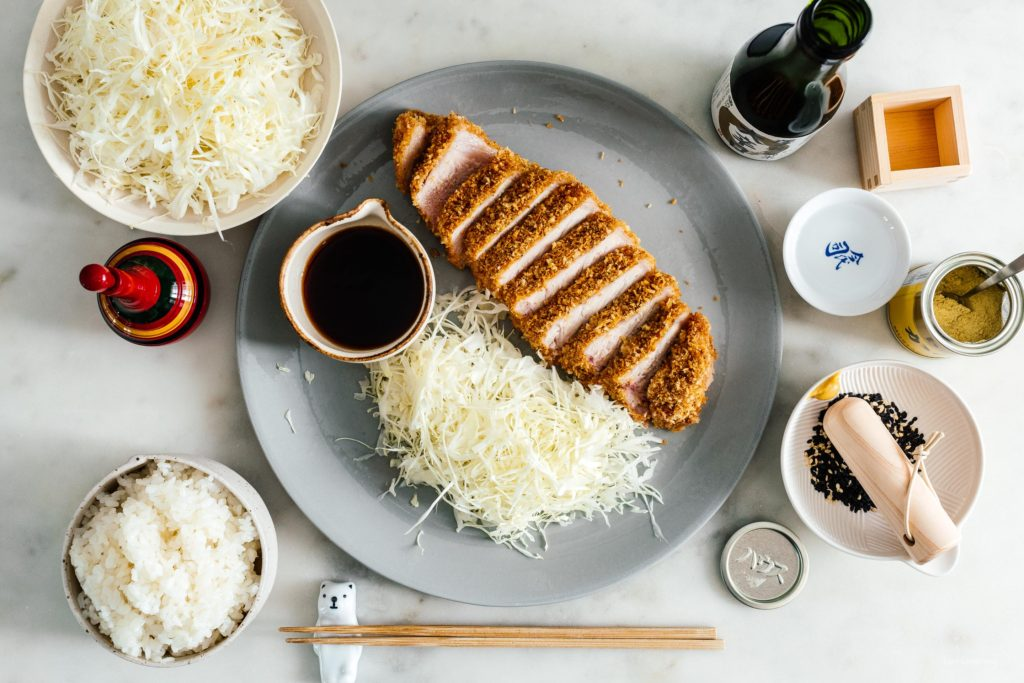 Easy oven baked pork tonkatsu: An extra thick, super juicy pork chop done up tonkatsu style, with light and crispy panko, only baked instead of deep-fried. #japanesefood #japanese #tonkatsu #porkchop #pork #recipes #ovenbaked #dinner #easydinner